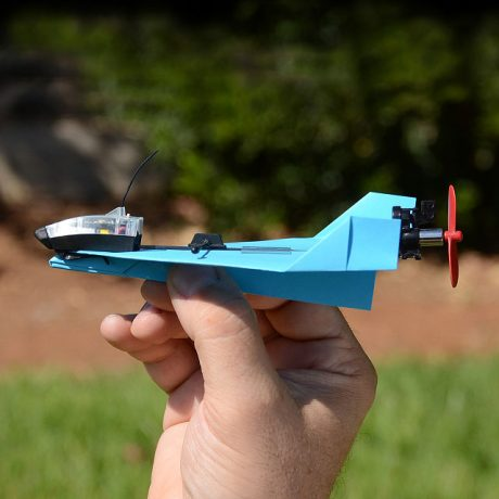 Tech but outdoors! Image of an airplane with a hand holding it outside in green grass